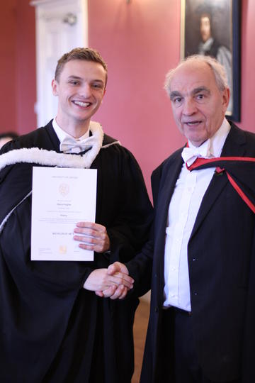 Student receiving graduation certificate from Master of St Benet's Hall